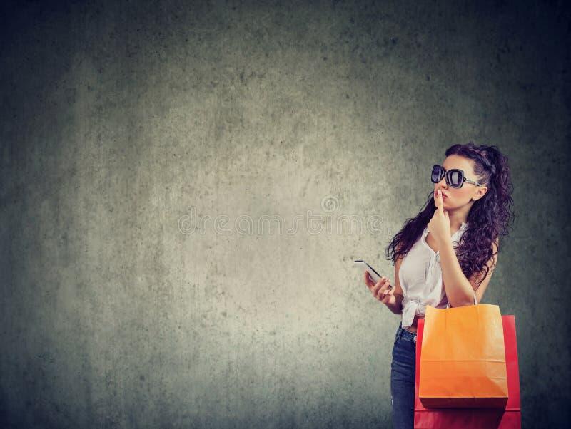 Femme à la mode réfléchie avec les paniers et le téléphone photos libres de droits