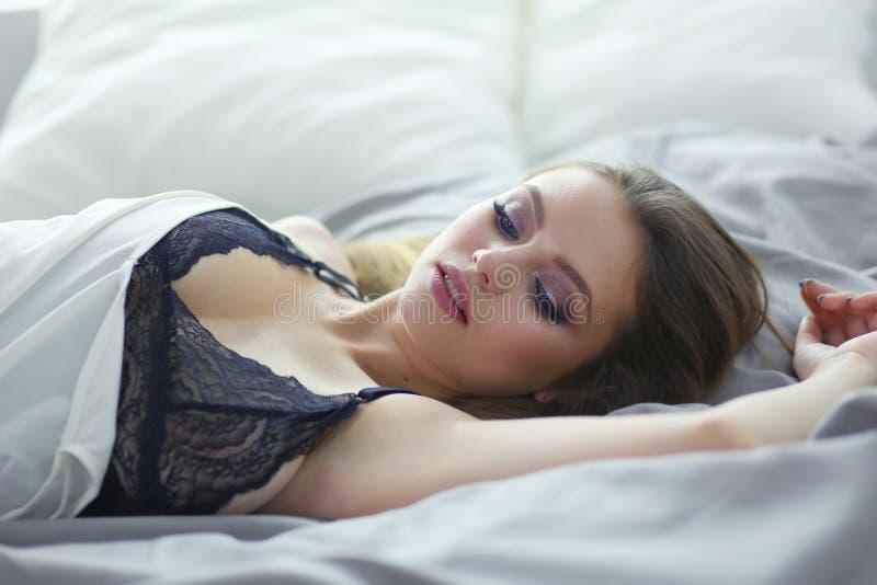 Femme à la mode sexy de portrait sur le lit images stock