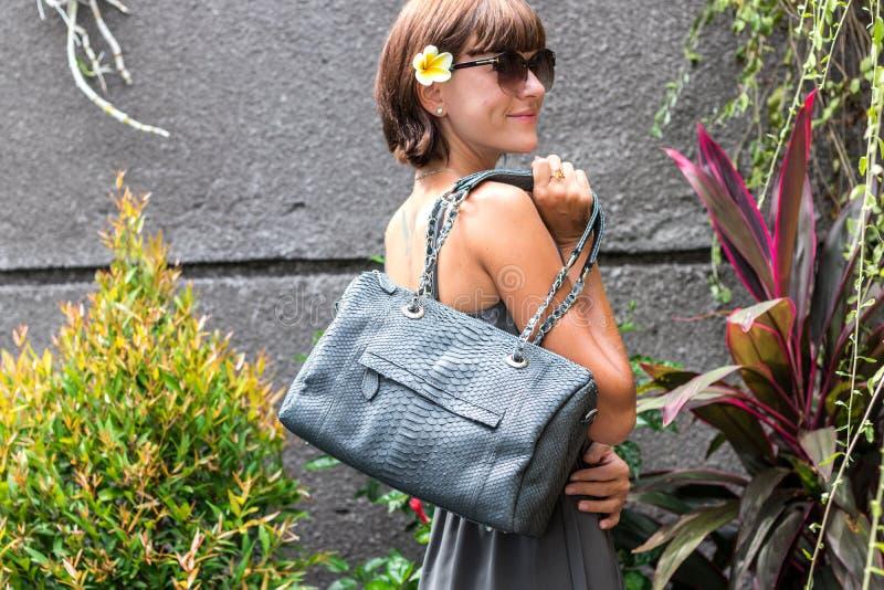 Femme à la mode tenant le sac élégant de luxe de python de peau de serpent Équipement élégant Fermez-vous de la bourse dans des m image stock