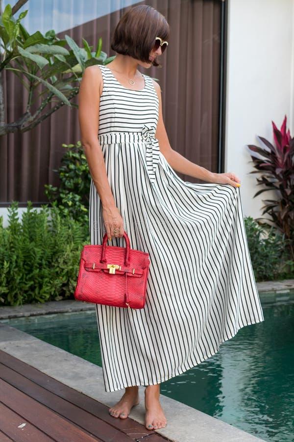 Femme à la mode tenant le sac de luxe de python de peau de serpent Équipement élégant Fermez-vous de la bourse dans des mains de  photo stock