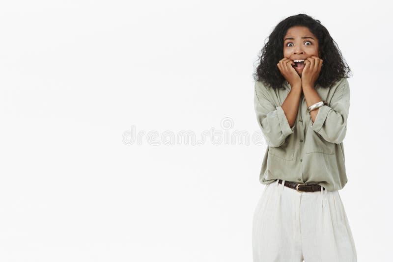 Femme à la peau foncée seing le grand insecte dans la chambre criant de l'effroi tenant des doigts dans des ongles acérés de bouc photo libre de droits