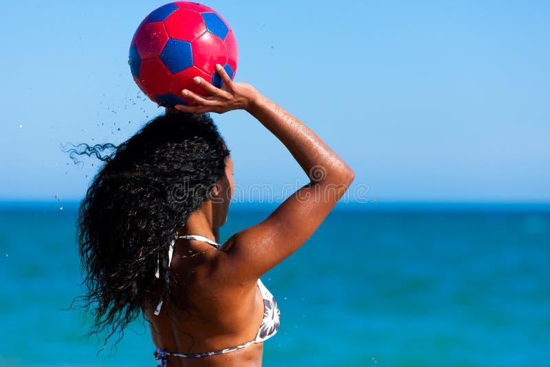 Femme à la plage jouant au football photographie stock libre de droits