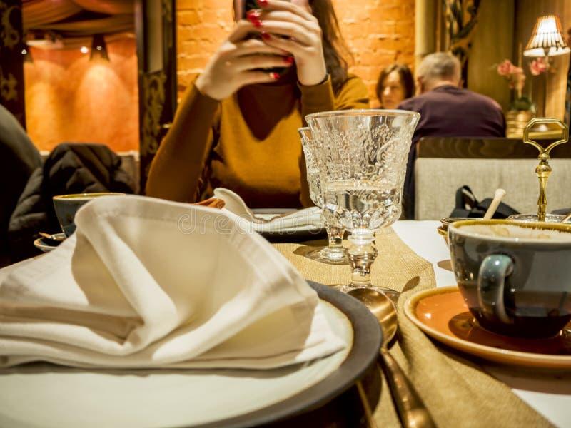 Femme à la table et plats dans le restaurant photos stock