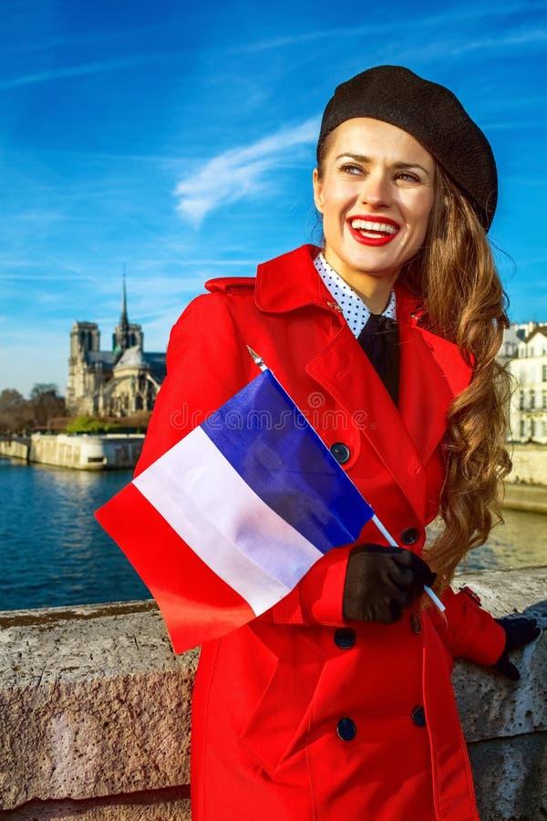 Femme à Paris avec le drapeau français examinant le distanc images stock