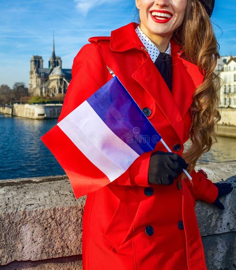 Femme à Paris avec le drapeau français examinant le distanc photographie stock libre de droits