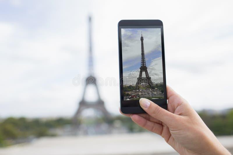 Femme à Paris prenant des photos devant Tour Eiffel, cellule pH photographie stock
