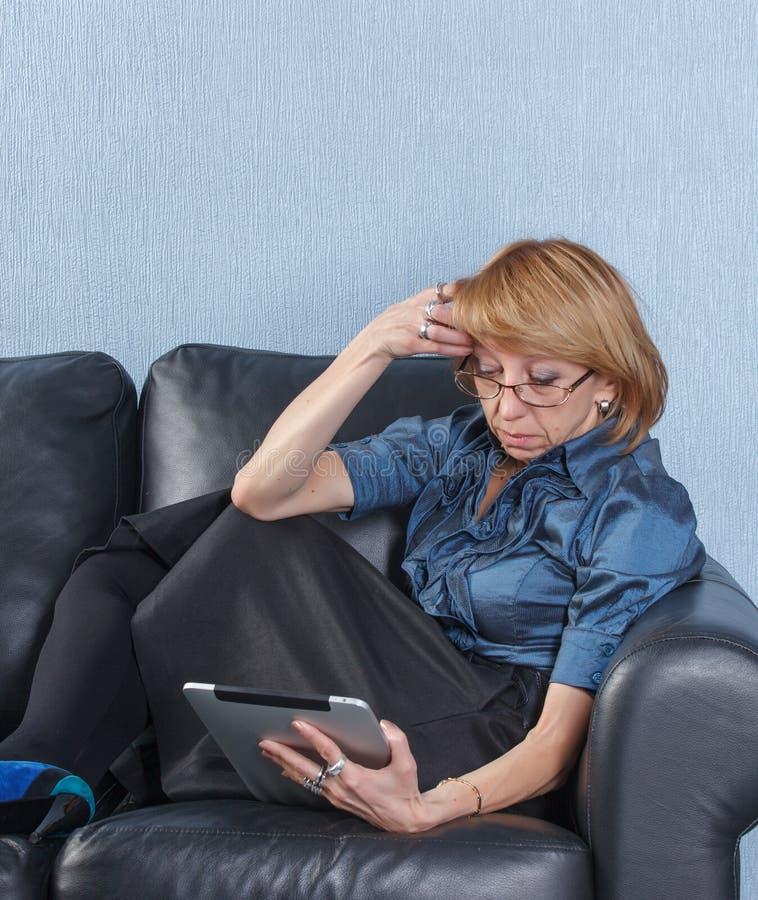 Femme âgé moyen à l'aide du PC de tablette sur le divan photo libre de droits