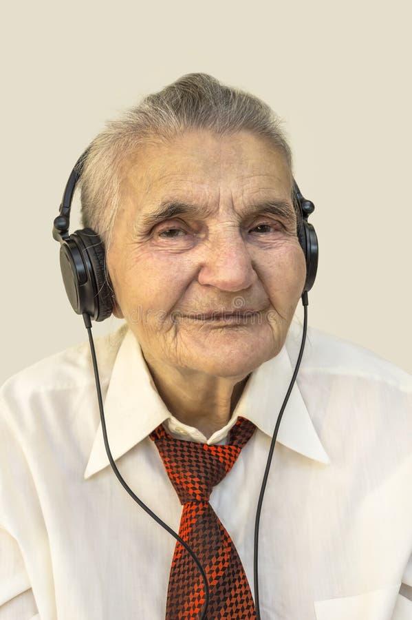 Femme âgée écoutant la musique photos stock