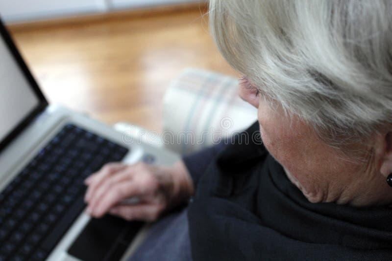 Femme âgée avec l'ordinateur portatif photos stock