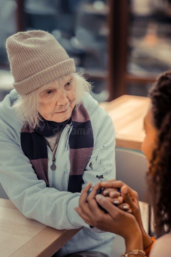 Femme âgée malheureuse recevant l'aide des personnes photo stock