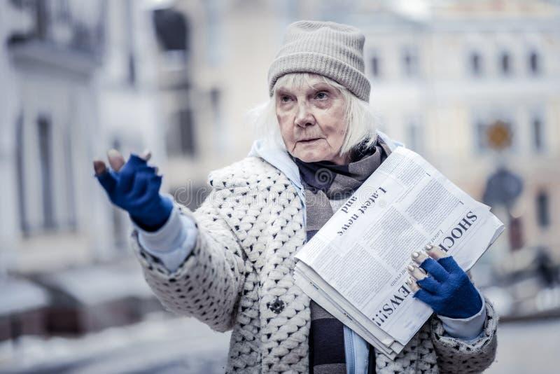 Femme âgée malheureuse vendant des journaux aux gens image libre de droits