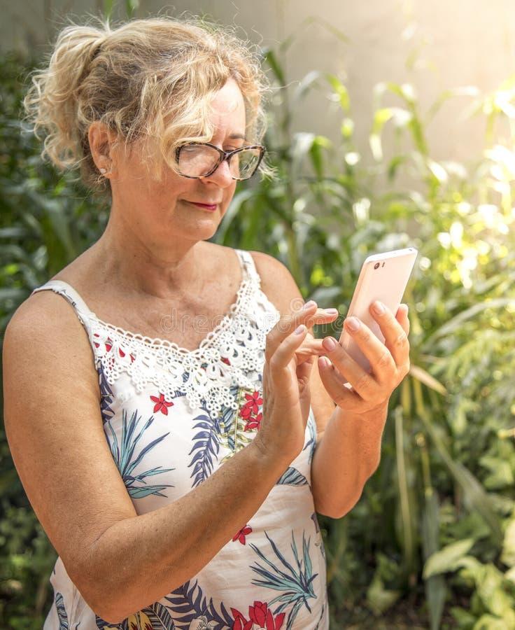 Femme âgée moyenne à l'aide du téléphone portable photos libres de droits
