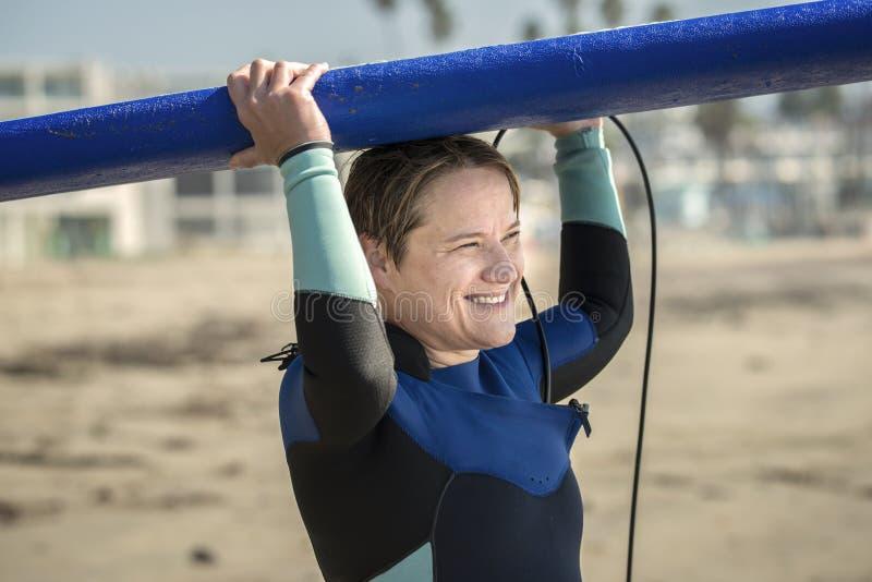 Femme âgée moyenne à la plage portant la planche de surf bleue image stock