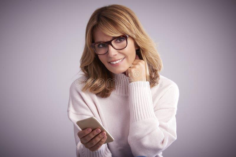 Femme âgée moyenne avec son téléphone portable images stock