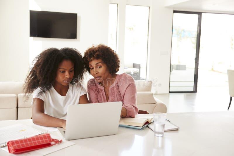 Femme âgée moyenne d'Afro-américain aidant sa fille adolescente avec le travail, vue de face images stock