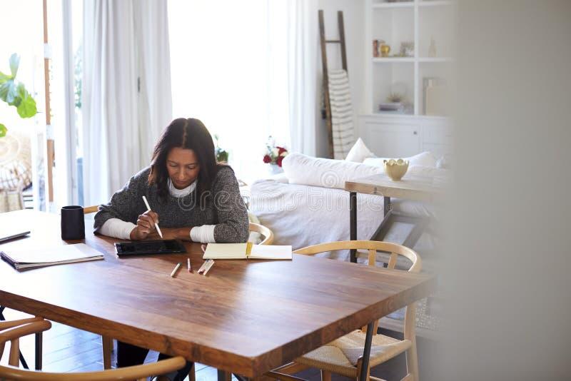 Femme âgée moyenne d'Afro-américain s'asseyant à une table dans sa salle à manger utilisant un stylet avec une tablette, vue de l images libres de droits