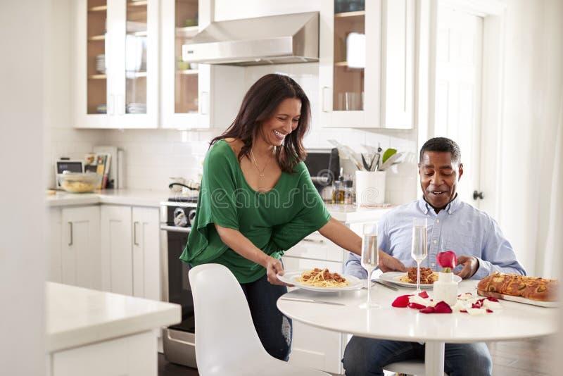 Femme âgée moyenne de femme d'Afro-américain servant à son associé un repas romantique dans leur cuisine, foyer sélectif images libres de droits