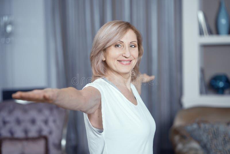 Femme âgée moyenne faisant le yoga à la maison images libres de droits