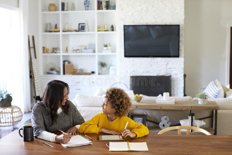 Femme âgée moyenne s'asseyant à une table dans la salle à manger faisant le travail avec sa petite-fille, vue élevée photos libres de droits