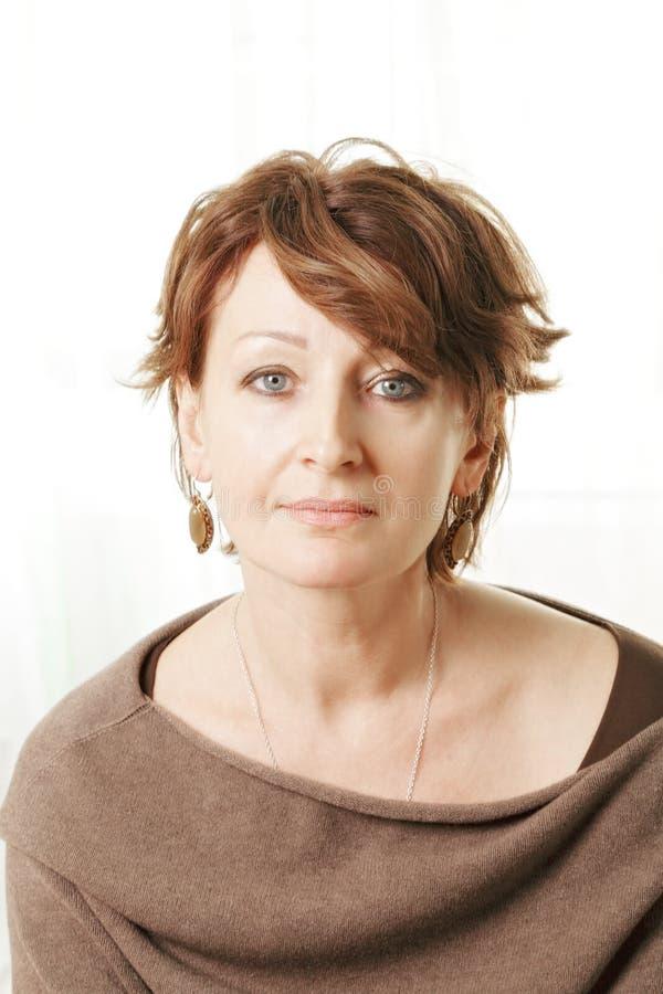 Femme âgée par milieu dans le chandail brun photo libre de droits