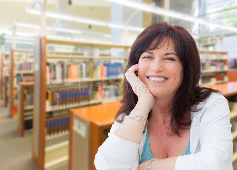 Femme âgée par milieu de sourire à l'intérieur de la bibliothèque photographie stock