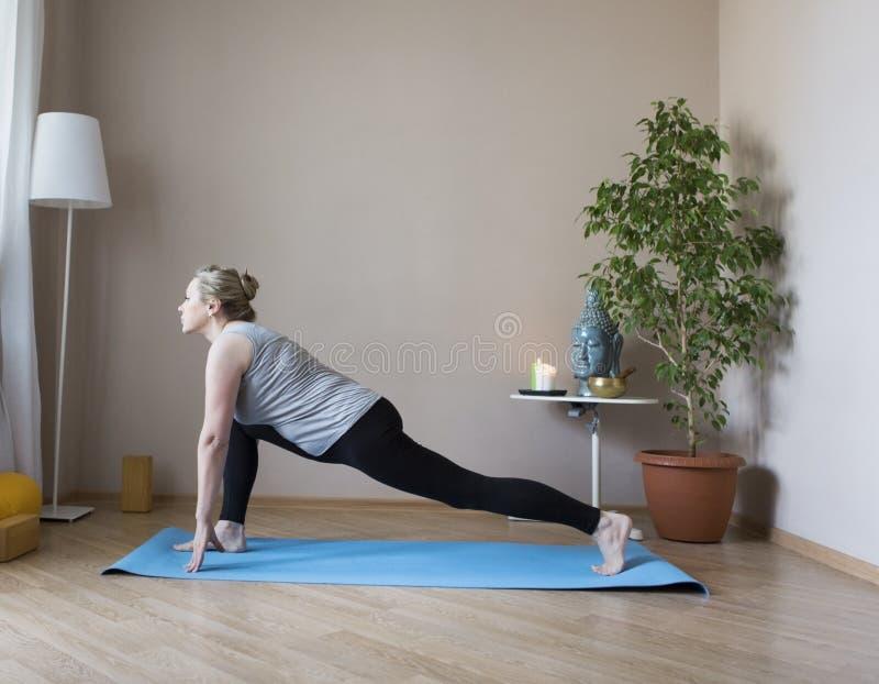Femme âgée par milieu faisant le yoga à l'intérieur images libres de droits