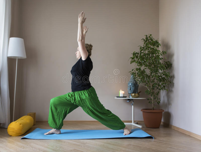 Femme âgée par milieu faisant le yoga à l'intérieur photos stock