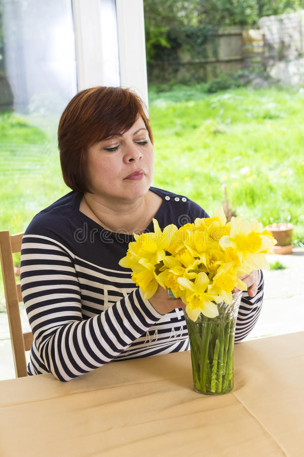 Femme âgée par milieu heureux avec le bouquet jaune images stock