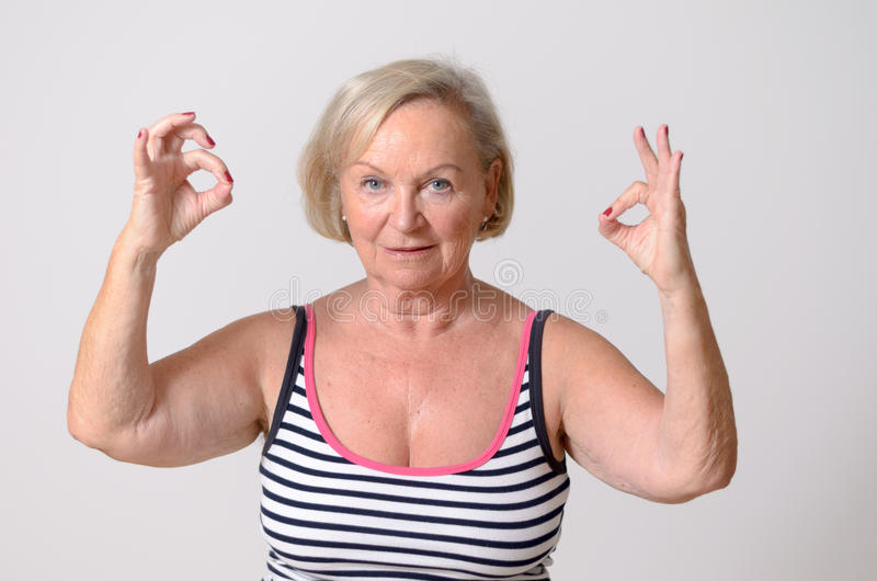 Femme âgée par milieu montrant deux signes corrects de main image libre de droits