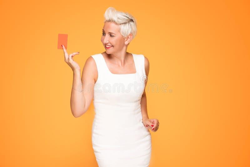 Femme âgée par milieu posant avec la carte de crédit photos stock