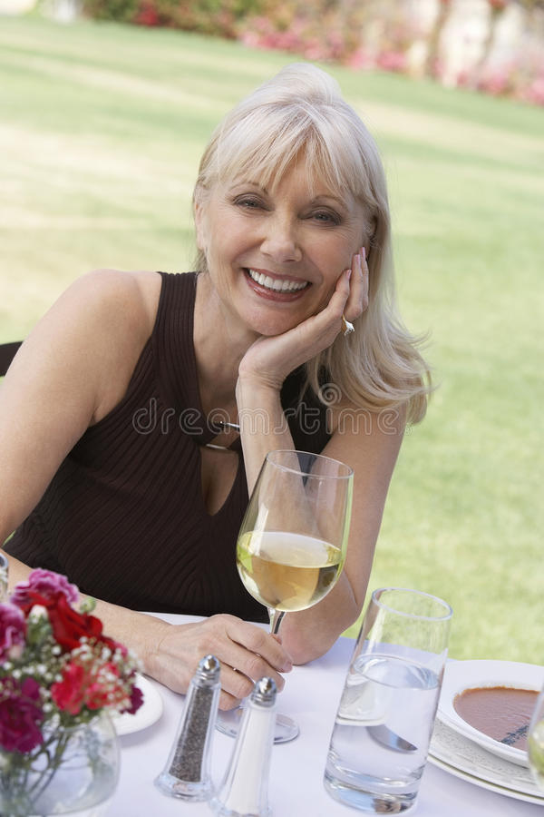 Femme âgée par milieu s'asseyant avec le verre à vin au Tableau extérieur image libre de droits