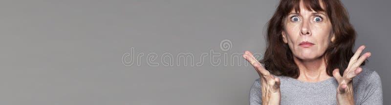 Femme âgée par milieu tendue exprimant la désillusion, bannière grise de l'espace de copie photographie stock libre de droits