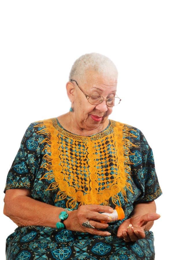 Femme âgée prenant des pillules images libres de droits