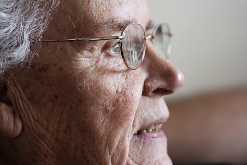 Femme âgée regardant et souriant fixement du côté photo libre de droits