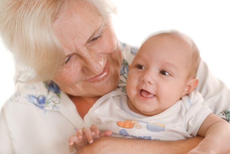 Femme âgée retenant un nouveau-né dans des ses bras photographie stock libre de droits