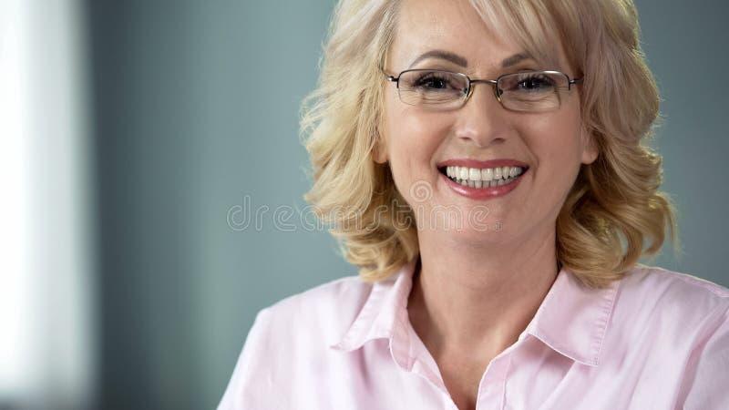 Femme âgée souriant sincèrement avec les dents blanches saines, services de soins dentaires photos stock