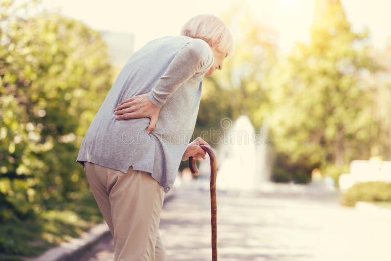Femme âgée triste se penchant sur le bâton de marche photos libres de droits