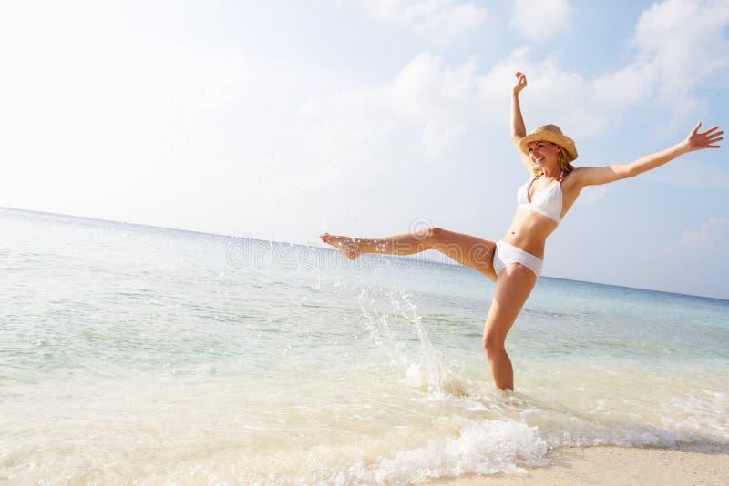 Femme éclaboussant en mer des vacances de plage images libres de droits