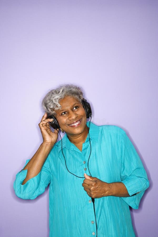 Femme écoutant des écouteurs. photographie stock libre de droits