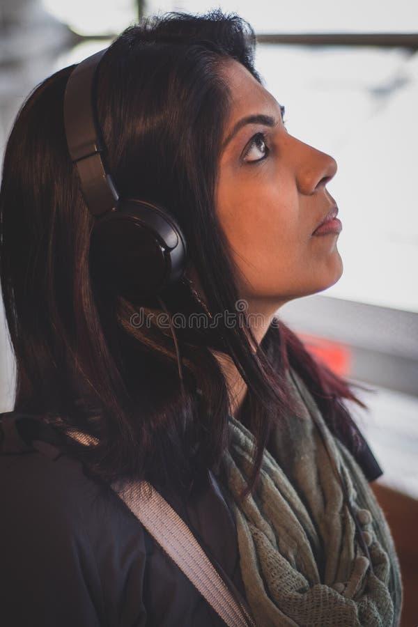 Femme écoutant l'audioguide sur des écouteurs photographie stock
