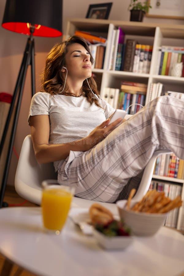 Femme écoutant la musique à un téléphone intelligent photo stock