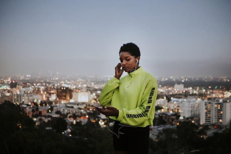 Femme écoutant la musique d'un téléphone image stock