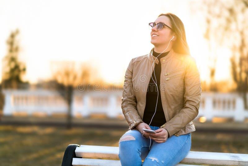 Femme écoutant la musique dehors Séance de sourire heureuse de dame photos stock