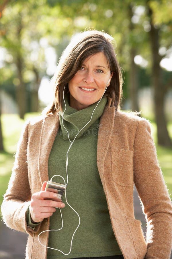 Femme écoutant le MP3 tout en marchant en stationnement photographie stock