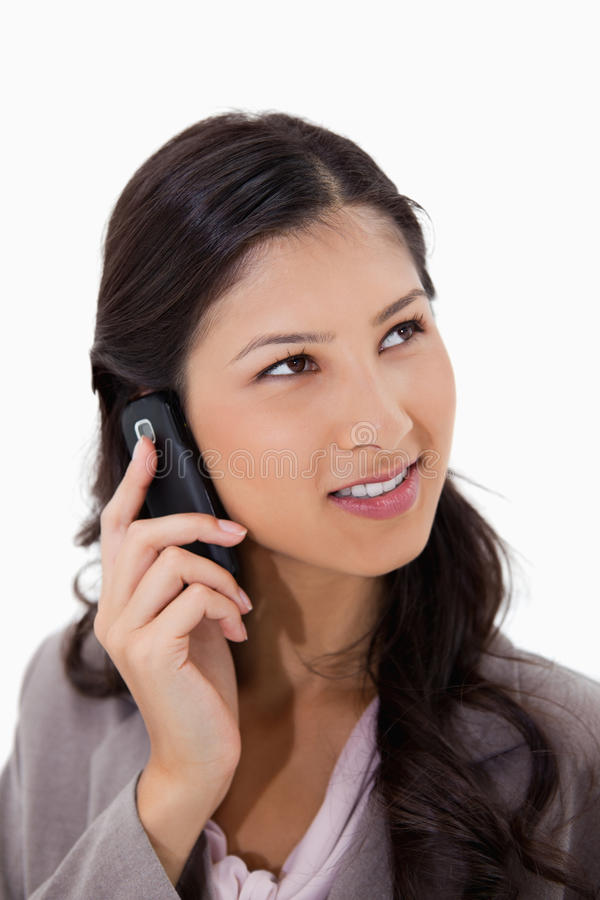 Femme écoutant le visiteur au téléphone photo stock