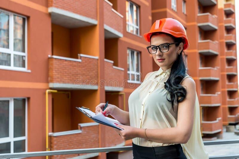 Femme écrivant sur le presse-papiers sur le chantier photo stock