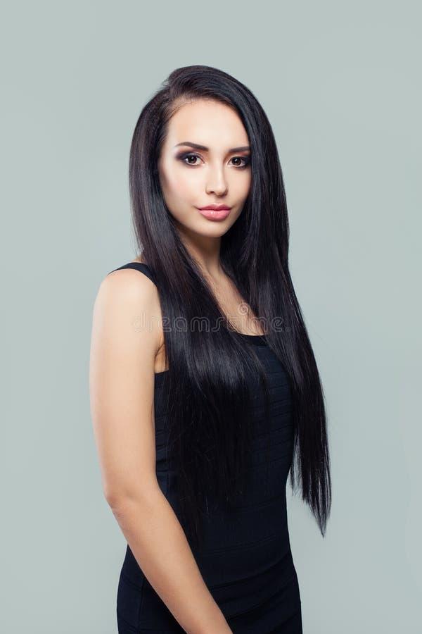 Femme élégante avec de longs cheveux droits sains et maquillage portant la robe noire images stock