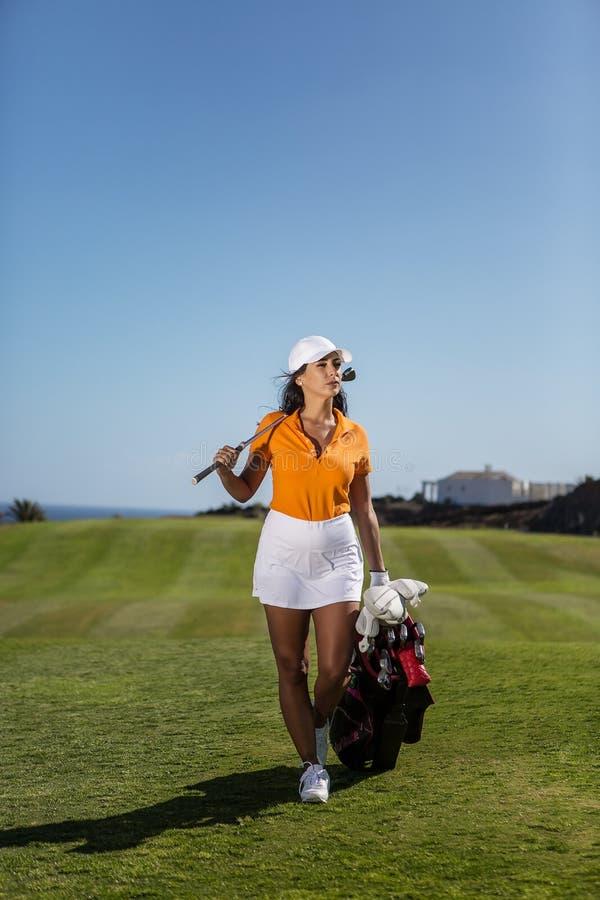Femme élégante avec des conducteurs de golf sur le champ photographie stock libre de droits