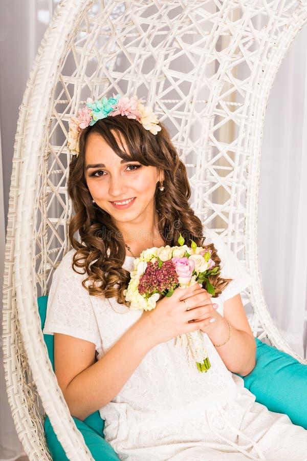 Femme élégante avec des fleurs dans un intérieur blanc image libre de droits