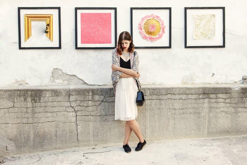 Femme élégante avec l'équipement de boho posant au mur avec l'art de rue dedans photographie stock libre de droits